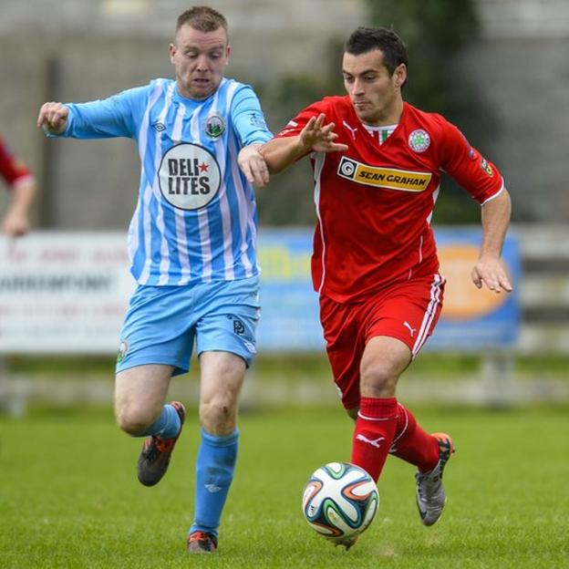 Timothy Grant of Warrenpoint Town in action against Cliftonville striker David McDaid