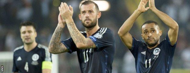 Russell Martin, Steven Fletcher and Ikechi Anya salute the Scotland fans after the match