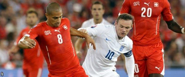 England's Wayne Rooney, right, fights for the ball with Switzerland's Gokhan Inler