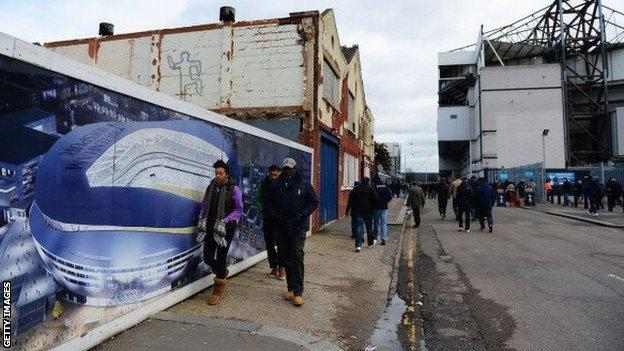Fans walk past a mural depicting design for a new Tottenham Hotspur stadium