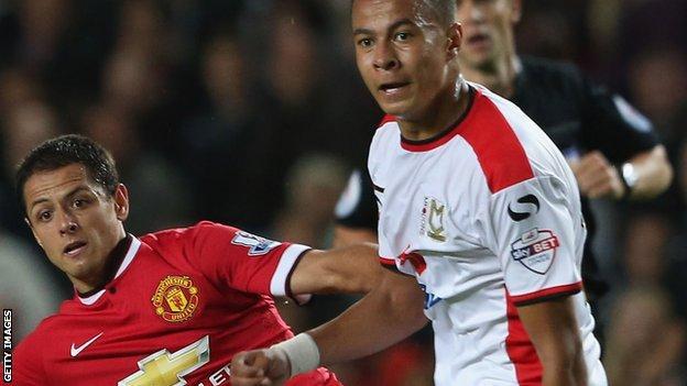 Dele Alli (left) tussles with Manchester United's Javier Hernandez