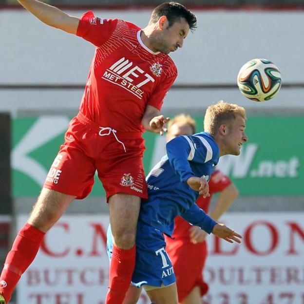 Portadown midfielder Michael Gault challenges for a high ball with John Currie of Ballinamallard United