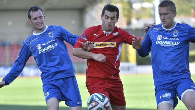 Dermot McCaffrey and David Armstrong challenge Cliftonville striker David McDaid at Solitude