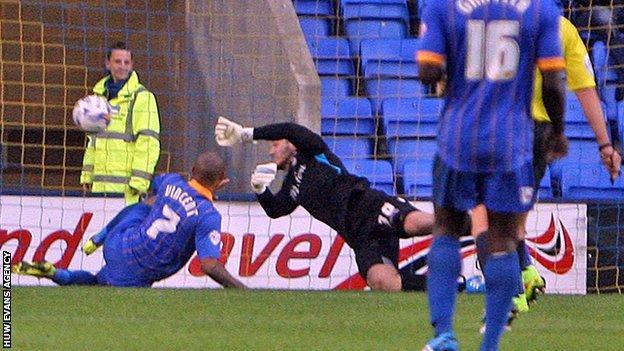 Newport goalkeeper Joe Day dives full length to deny Shrewsbury