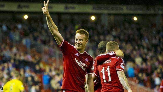 Adam Rooney salutes the Aberdeen support after netting a hat-trick against Livingston.