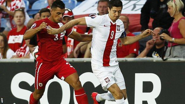 "Joseph Chipolina (left) vies with Poland""s forward Robert Lewandowski"