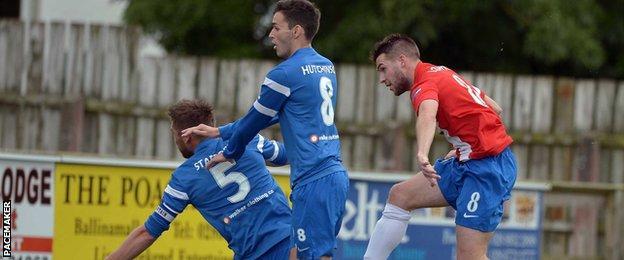 Linfield's Stephen Lowry beats Mark Stafford and Stuart Hutchinson of Ballinamallard United