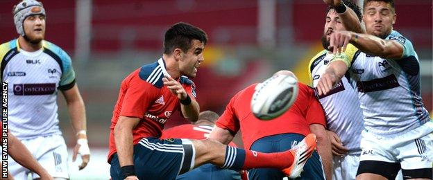 Ospreys scrum-half Rhys Webb charges down the kick of Munster's Conor Murray