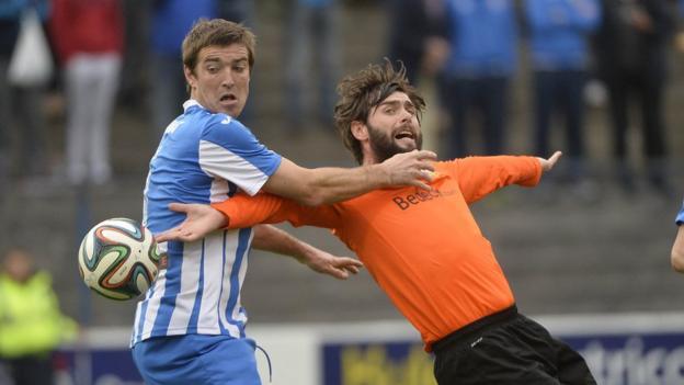Coleraine defender Steven Douglas attempts to halt the progress of Glenavon player-manager Gary Hamilton