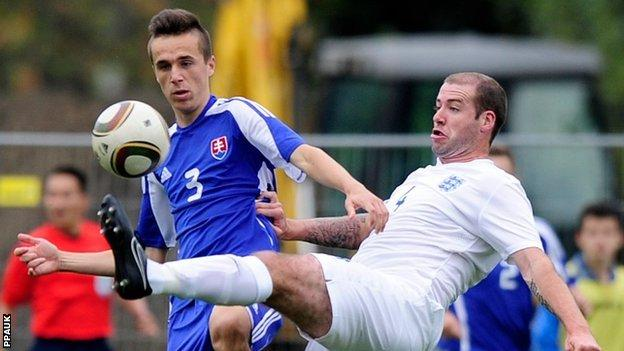 England's Mark Wolfenden (St Mary's) is tackled by Slovakia's Robert Dicky .