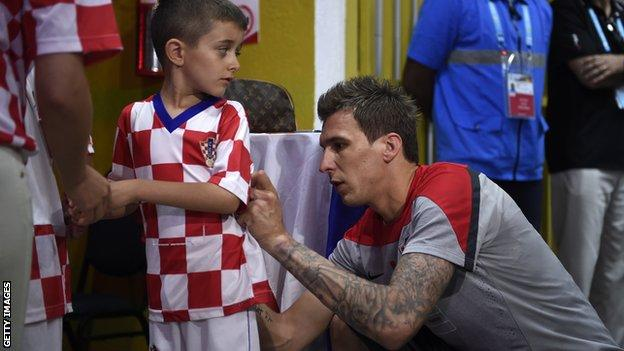 Mario Mandzukic signs a young fan's shirt