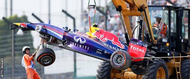 Marshalls remove the wrecked car belonging to Daniel Ricciardo of Australia and Infiniti Red Bull Racing during practice for the Japanese Formula One Grand Prix at Suzuka.