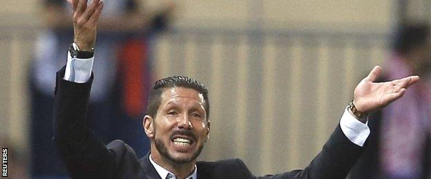 Diego Simeone raises both hands reacting to a decision in Atletico Madrid's Champions League match against Juventus