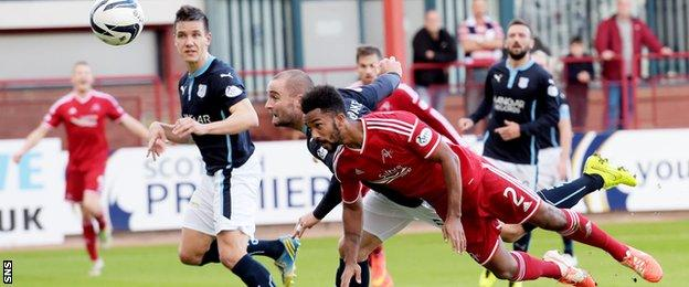 James McPake heads into his own net under pressure from Shay Logan