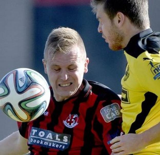Crues striker Jordan Owens beats Cliftonville's Jaimie McGovern to the ball at Seaview
