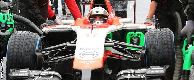 Crew members of Marussia driver Jules Bianchi push his car to the grid