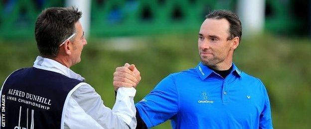 Oliver Wilson of England is congratulated by his caddie John Dempster
