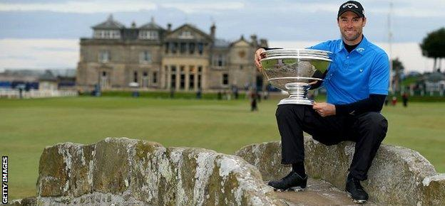 Oliver Wilson of England holds the trophy aloft on the Swilcan Bridge on the 18th hole