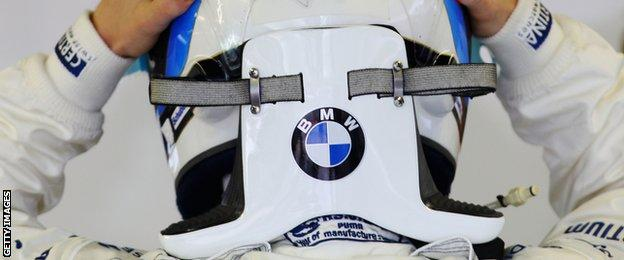 Nick Heidfeld is seen putting on his helmet with HANS safety device attached