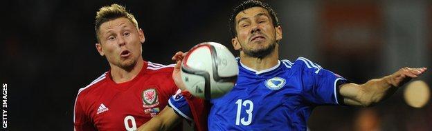 Simon Church battles for the ball with Mensur Mujdza