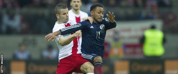 Ikechi Anya tussles for possession with Poland's Tomasz Brzyski in the friendly match in Warsaw in March
