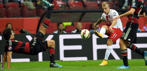 Poland's midfielder Kamil Grosicki shoots past Germany's Mats Hummels and Christoph Kramer