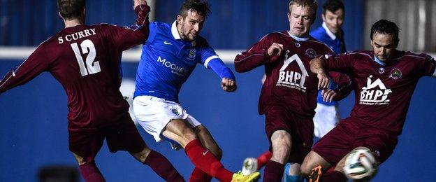Linfield striker Andy Waterworth gets his shot away despite pressure from three Institute players