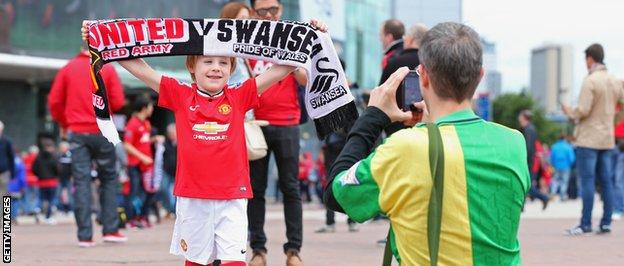A young Manchester United fan poses for a photo outside Old Trafford