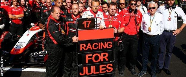 Max Chilton and his Marussia team members stand in respect for Jules Bianchi in Russia