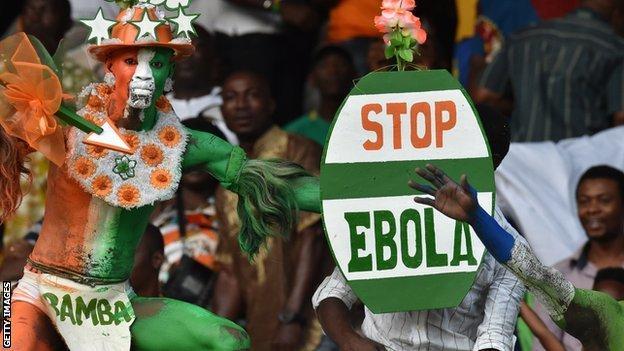 "An Ivory Coast fan holds up a ""Stop Ebola"" placard"