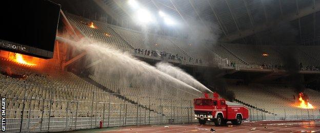 March 2012: A fire engine sprays water on fires set in the stadium during clashes between riot police and Panathinaikos supporters during the Athens derby
