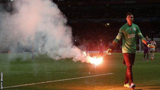 Fernando Muslera of Galatasaray clears a flare