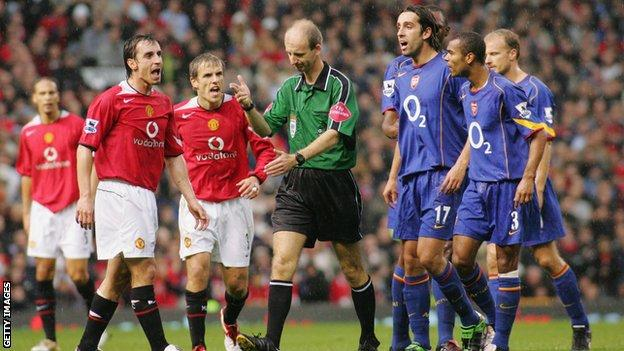 Manchester United and Arsenal players surround Mike Riley