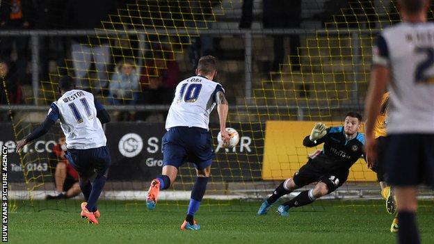 Newport County goalkeeper Joe Day dives to keep out the penalty of Southend's Myles Weston
