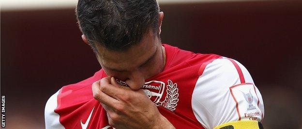 Robin van Persie kisses the Arsenal badge