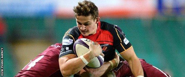 Dragons' Hallam Amos is tackled by Alex Tait and Chris Harris of Newcastle