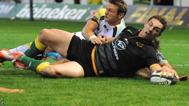 Northampton winger George North beats Ospreys' fly-half Dan Biggar, among others, to score his fourth try