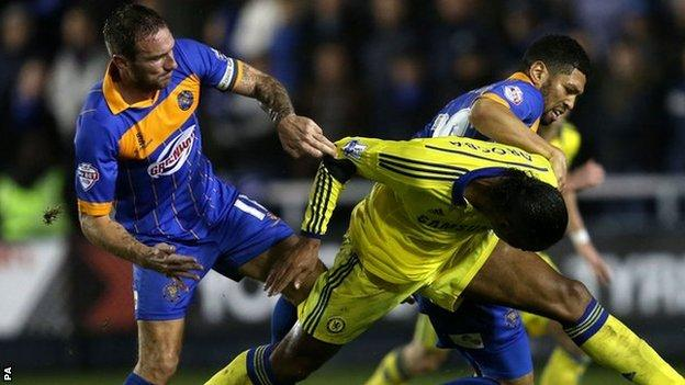 Shrewsbury Town skipper Liam Lawrence gets to grips with Didier Drogba
