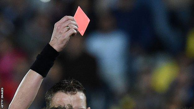 Referee holds red card