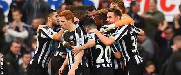 Newcastle players celebrate taking the lead against Liverpool
