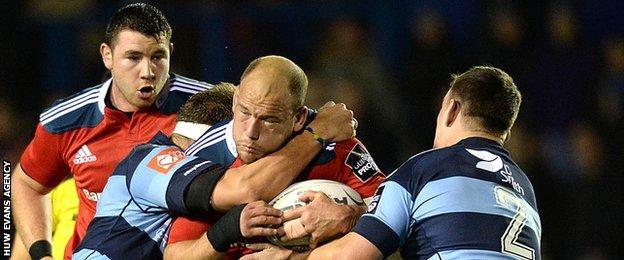 BJ Botha of Munster is tackled by Jarrad Hoeata