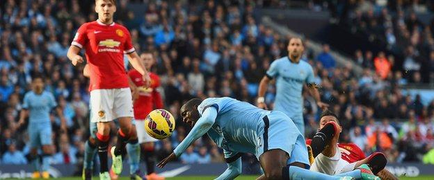 Yaya Toure goes down under a challenge from Marcos Rojo
