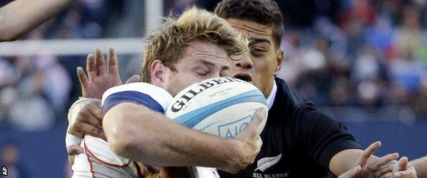 USA's Tom Coolican is tackled by All Blacks' Augustine Pulu