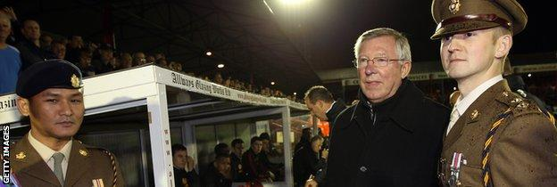 Two soldiers from Aldershot garrison with then Manchester United manager Sir Alex Ferguson in 2011