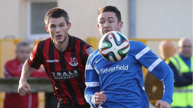 Craig McClean prepares to challenge Liam Martin during Crusaders' 1-1 draw with Ballinamallard at Ferney Park