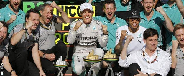 Nico Rosberg (C) of Germany and second placed Mercedes Formula One driver Lewis Hamilton (3rd R) of Britain pose for the official photo with staff after the Brazilian Grand Prix in Sao Paulo November 9, 2014.