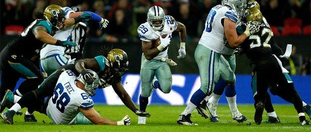 DeMarco Murray bursts through a hole in the Jacksonville defence