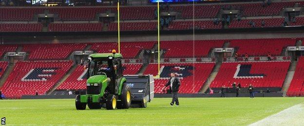 Ground staff work on Wembley pitch