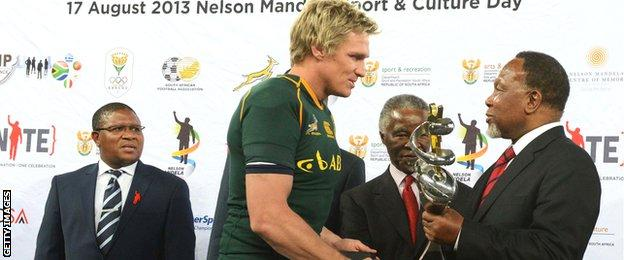 Boks captain Jean de Villiers receives a trophy from former South Africa president Thabo Mbeki and then deputy president Kgalema Motlanthe after victory over Argentina in Soweto in August 2013