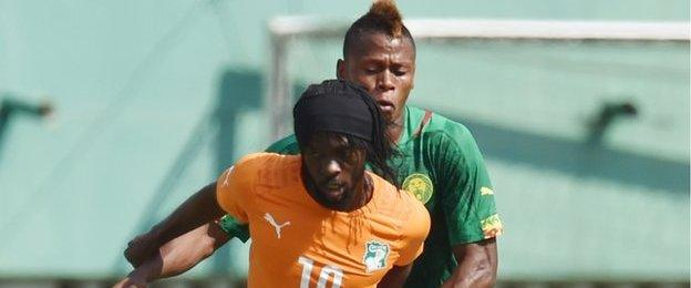 Ivory Coast's Gervinho (front) tussles with Cameroon's Clinton Ndjie